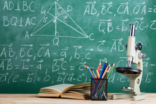 Education and sciences concept - books on the teacher desk in the auditorium, chalkboard on the background.