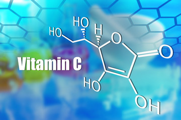 Molecular formula and the inscription vitamin C on a blue background. Vitamin supplement. Use of vitamin C for colds. Sources of vitamin C. Ascorbic acid and its use in the food industry.