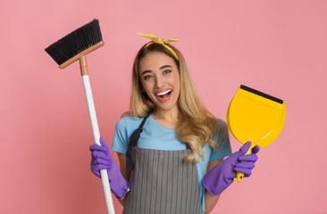 House cleaning concept. Smiling housewife with broom and shovel in hands