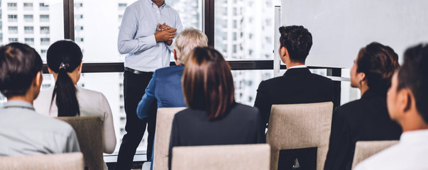 Businessman standing in front of group of people in consulting meeting conference seminar at hall or seminar room.presentation and coaching concept