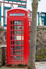 Fotorolgordijn Rood, zwart, wit Red english telephone booth in front of a stone wall in Bad Muenstereifel