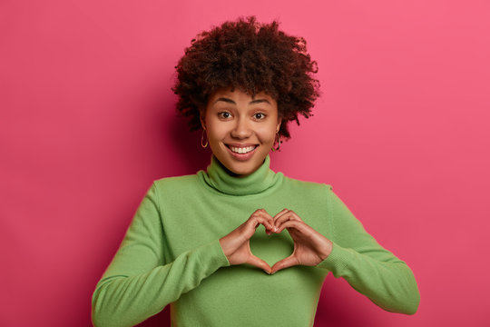 Pleased cheerful dark skinned Afro American woman shapes heart, confesses in love and expresses sympathy, smiles broadly, shows white teeth, wears green turtleneck, isolated on pink background