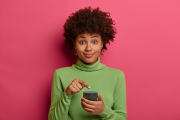 Afro American teenager points at modern smartphone display, recommends download new application, advertises new game, received notification in online chat, wears casual green jumper, poses indoor