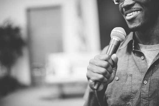 Greyscale shot of a happy African-American male talking on the microphone at the church
