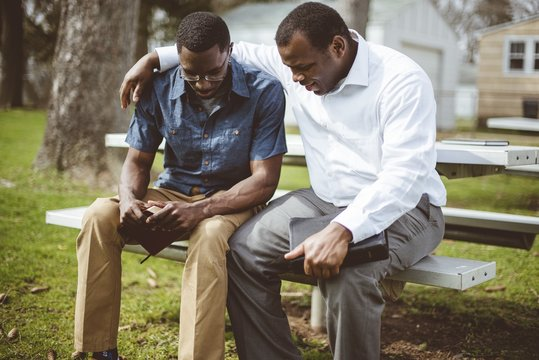 African-American male friends sitting on the bench praying with the Bible in their hands