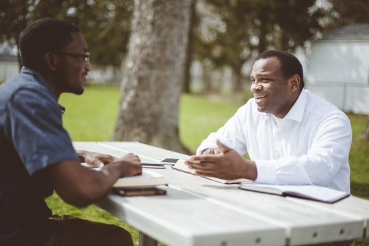 African-American male friends sitting at the table and reading the Bible at the table