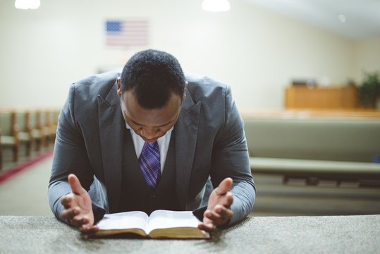 African-American male praying with his head down looking at the Bible at the church
