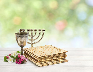 Matzo, wine, menorah and pink flowers apple tree for passover celebration on white background with space for text