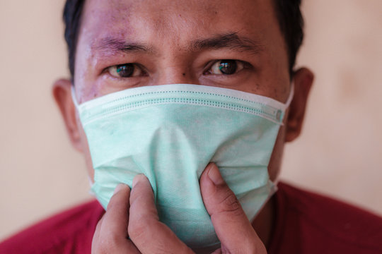 Indonesian man wearing a medical face mask to prevent himself from attacked diseases caused by viruses, such as coronavirus or covid-19 and avian influenza, which become a world pandemic.
