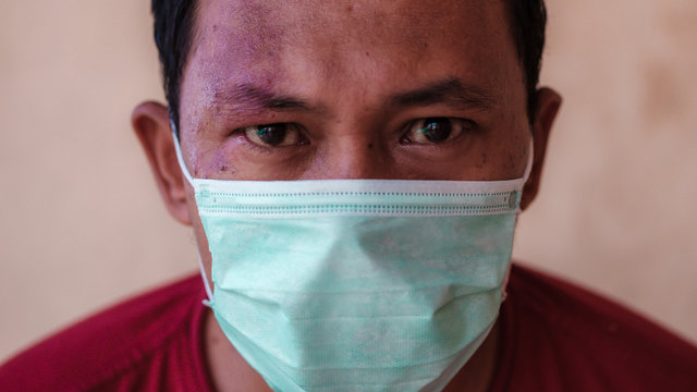 Indonesian man wear medical face mask masks to prevent himself from diseases outbreak caused by viruses, such as coronavirus or covid-19, which have become a global pandemic in 2020.
