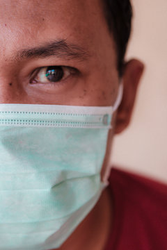 Asian man wearing a medical face mask to anticipate the spread of deadly diseases outbreak caused by viruses, such as coronavirus or covid-19 and avian influenza, which become a world pandemic.
