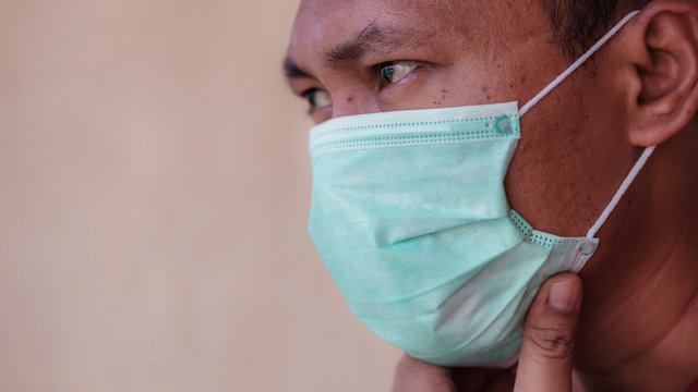 Asian man wearing a medical face mask to anticipate the spread of diseases outbreak caused by viruses, such as coronavirus or covid-19 and avian influenza, which become a world pandemic.