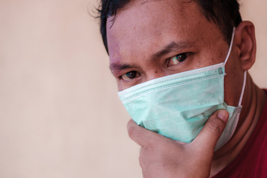 Indonesian man wearing a medical face mask to anticipate the spread of diseases caused by viruses, such as coronavirus or covid-19 and avian influenza, which become a world pandemic.