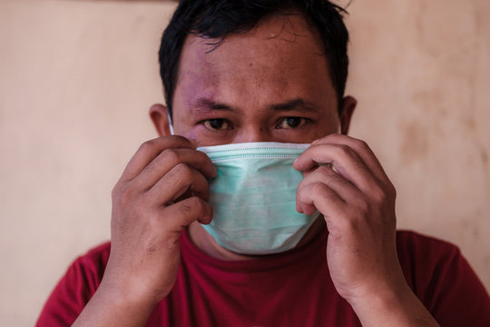 Asian man wearing a medical face mask to prevent himself the spread of diseases caused by viruses, such as coronavirus or covid-19 and avian influenza, which can become a world pandemic.