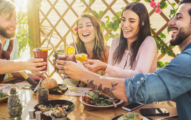 Happy friends lunching healthy food and drinking smoothies fresh fruits - Young people having fun eating in coffee brunch vintage bar - Health trends and lifestyle culture concept