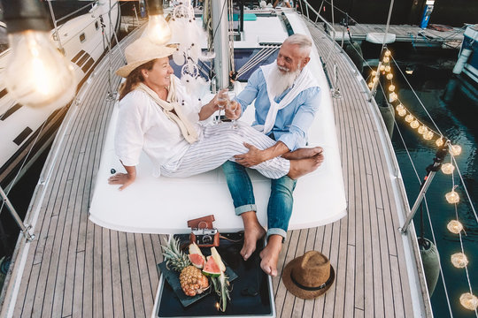 Senior couple toasting champagne on sailboat vacation - Happy mature people having fun celebrating wedding anniversary on boat trip - Love relationship and travel lifestyle concept