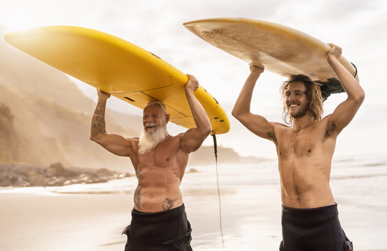 Happy friends surfing together on tropical ocean - Sporty people having fun during vacation surf day - Extreme sport lifestyle concept