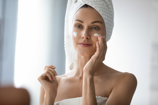 Head shot beautiful 30s lady looking in mirror, applying hydrating lotion creme on cheeks, finishing morning domestic skincare routine. Smiling woman grooming herself after showering in bathroom.
