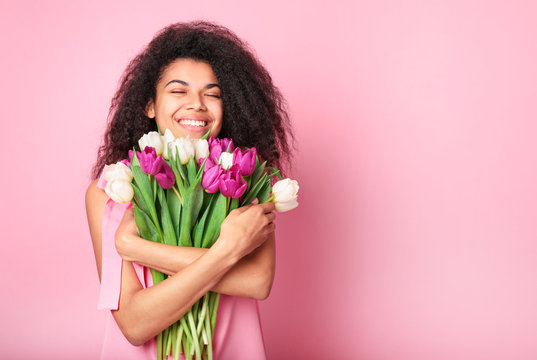 Young african woman with flowers on pink background. Women's day concept
