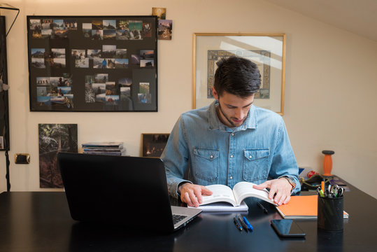 Male caucasian student following an online university lecture from home. Isolation during the coronavirus period