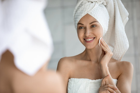 Head shot close up mirror reflection smiling beautiful woman wrapped in towel applying toner with cotton pad on skin face after bath. Happy young lady doing morning skincare routine after shower.