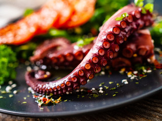 Fried octopus and vegetables on wooden table