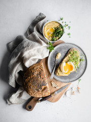 A spread of bread, hummus, and a soft boiled egg on a wood cutting board, surrounded by grey cheesecloth and garnished with parsley