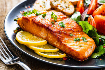 Fried salmon steak with potatoes and vegetables on wooden table Papier Peint