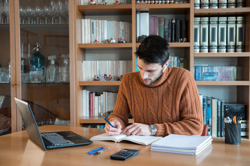 Young male studying for university at home via online lessons during the coronavirus quarantine....