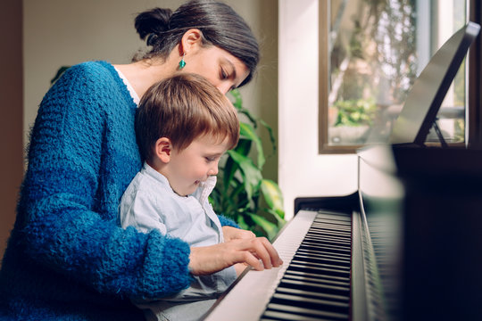 Family lifestyle spending time together indoors. Children with musical virtue and artistic curiosity. Educational musical activities for little kid. Mom teaching her son at home piano lessons.
