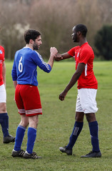 Players avoid hand shakes as they play park football at Hackney Marshes in London