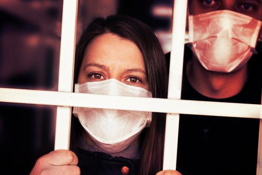 A woman and man in a mask , looking intently at the camera. Quarantine and isolation of patients with covid coronavirus 2019. Isolation grid, incarceration and illness. pandemics and epidemics