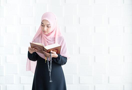 Beautiful young asian muslim woman reading quran