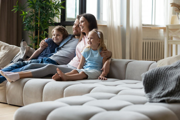 Happy young family with small kids sit relax on comfortable couch in living room watching movie together, smiling parents with daughter and son rest on cozy sofa enjoying weekend at home Wall mural