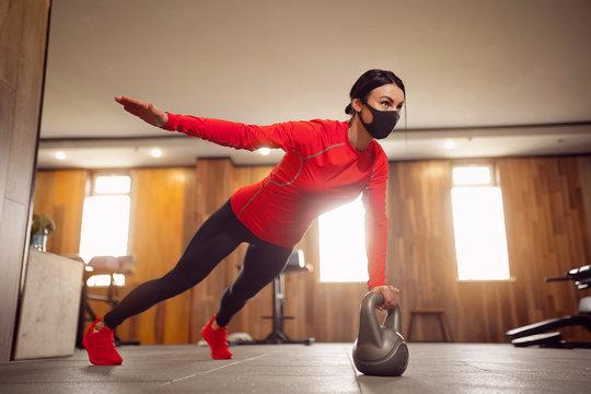 Sport Girl In Mask from Coronavirus doing Kettlebells Planking.