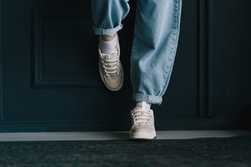Closeup view photography of two female legs isolated at black wall background. Woman wearing trendy fashionable blue denim jeans and sneakers with lacing. Wall mural