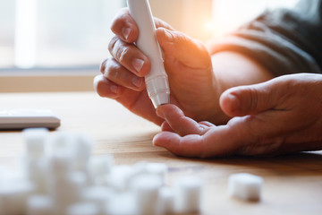 senior woman hands using lancet on finger at home to check blood sugar level, glucometer  and sugar cubes on wooden table close up, diabetes concept,  elderly health care, sunny morning