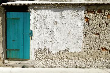 turkusowe stare drzwi w lekko zniszczonej kamienicy