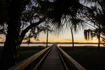 Sunset on Spring Island, South Carolina; view of a long dock leading out into the Callawassie River at sunset with palmetto trees and the marsh