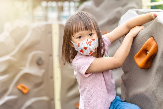 Portrait of young asian girl wearing mask playing outdoor climbing having fun