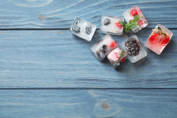 Ice cubes with different berries and mint on blue wooden table, flat lay. Space for text