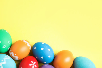 Colorful Easter eggs on yellow background, flat lay. Space for text