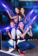 Group portrait of joyful young people with laser guns in their h