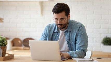 Serious man wearing glasses working on laptop online, sitting at table in kitchen, looking at computer screen, focused male using internet banking service, writing email, searching information Papier Peint