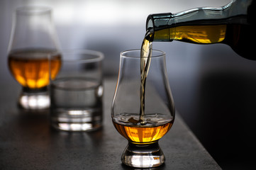 Fotorolgordijn Bar Pouring in tulip-shaped tasting glass Scotch single malt or blended whisky