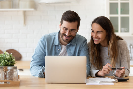 Happy young couple planning budget, reading good news in email, refund or mortgage approval, smiling woman and man looking at laptop screen, checking finances, sitting at table at home together