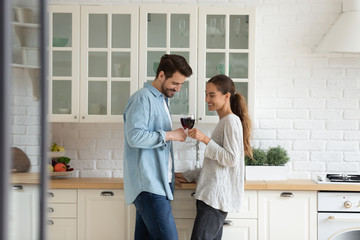 Happy loving couple clinking red wine glasses, standing in modern kitchen, beautiful wife and...