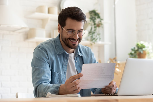 Smiling young man reading good news in paper notification, sitting at table with laptop, happy satisfied male wearing glasses holding document, job promotion, loan approval, great exam result