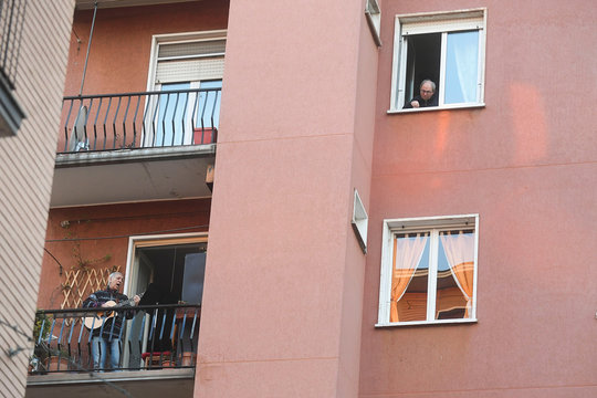A man plays the guitar from a balcony to raise morale on the sixth day of an unprecedented lockdown across of all Italy imposed to slow the outbreak of coronavirus in Milan