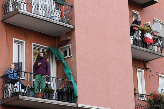 A man listens as a neighbor plays the guitar from a balcony to raise morale on the sixth day of an unprecedented lockdown across of all Italy imposed to slow the outbreak of coronavirus in Milan